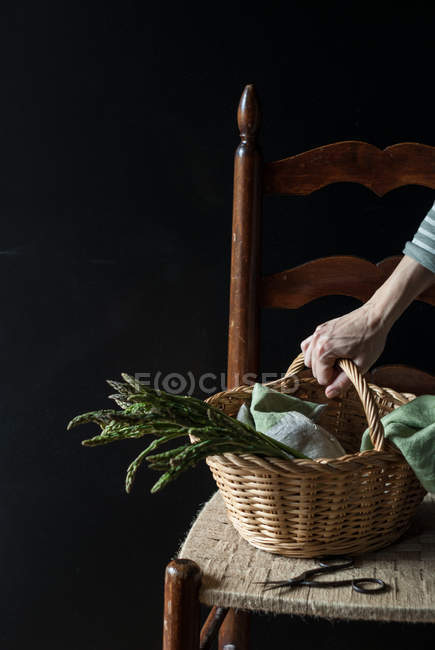 Людські руки, що тримає кошик свіжі зеленою спаржею на крісло на чорному фоні — стокове фото