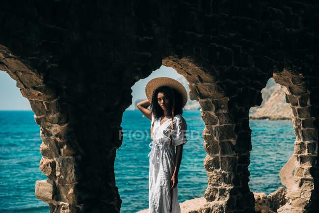 Черная женщина на древних руинах у моря — стоковое фото
