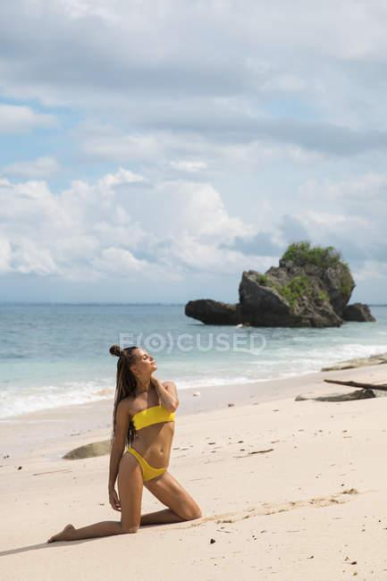 Giovane donna rilassata in bikini che propone sulla spiaggia sabbiosa — Foto stock