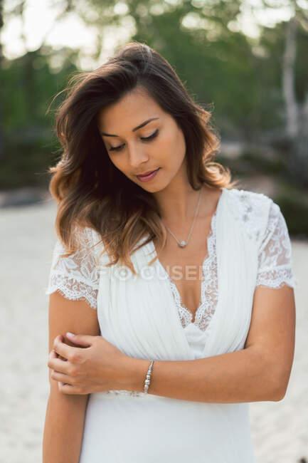 Очаровательная брюнетка в элегантном свадебном платье с ожерельем и смотрящая в камеру на улице — стоковое фото