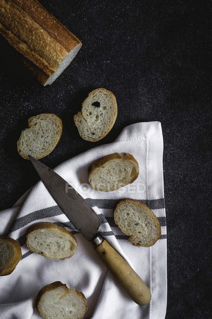 Partly sliced baguette with knife and kitchen towel on black surface — Stock Photo