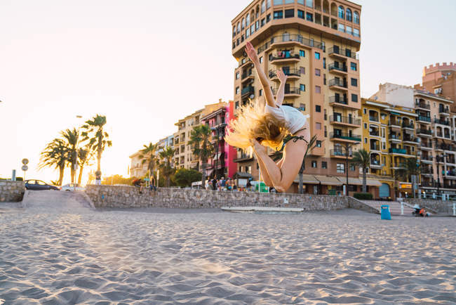 Flexible young woman jumping on beach with buildings on background — Stock Photo