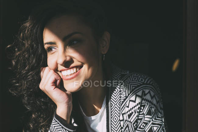 Smiling young woman looking out of window in sunlight — Stock Photo