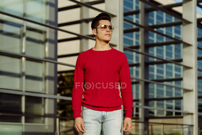 Attraktiver junger Mann steht vor Gebäude und schaut weg — Stockfoto