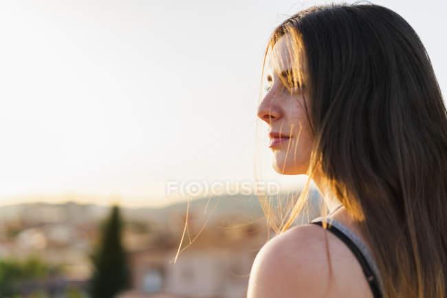Mulher pensativa elegante sentado olhando para longe na luz do sol — Fotografia de Stock