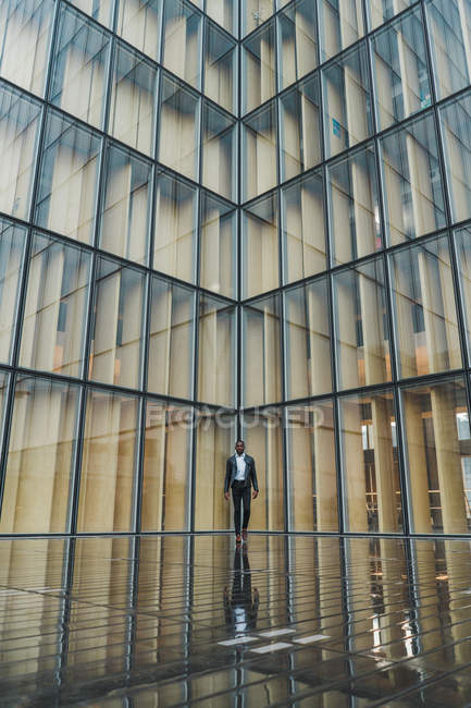 Homme d'affaires marchant sur la chaussée contre le bâtiment en verre moderne — Photo de stock