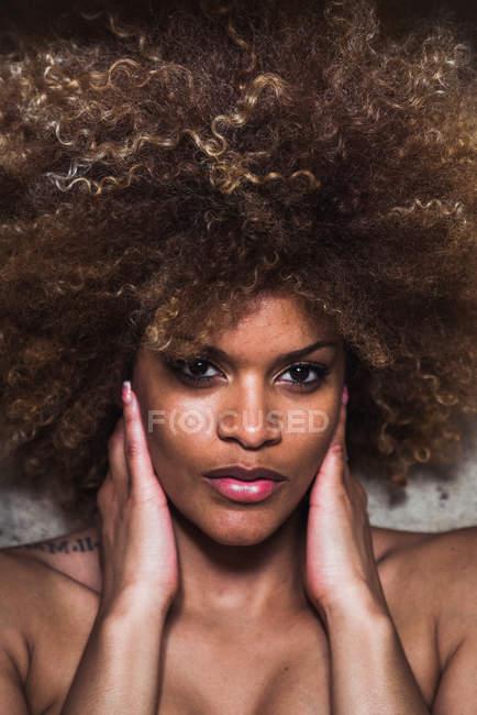 Gros plan de femme ethnique avec des cheveux Afro toucher le visage et en regardant sensuellement caméra — Photo de stock