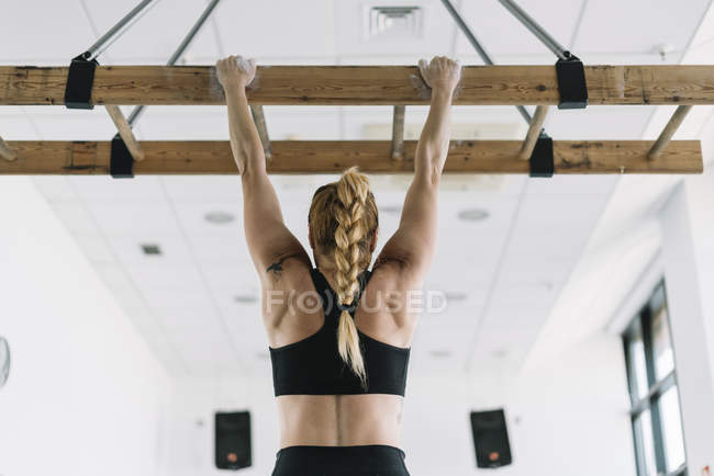 Back view of strong woman in sportswear hanging on wooden board in gym and pulling up — Stock Photo
