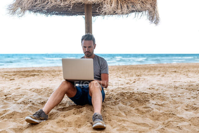 Man leaning on a straw umbrella at the beach working on the computer — Stock Photo