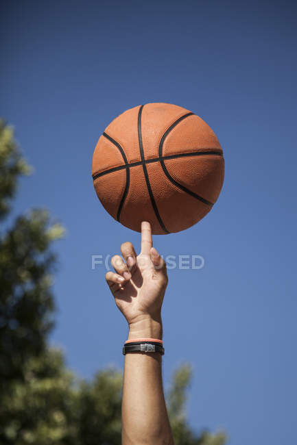 Мужская рука вращающийся баскетбол на пальце с голубым небом на фоне — стоковое фото