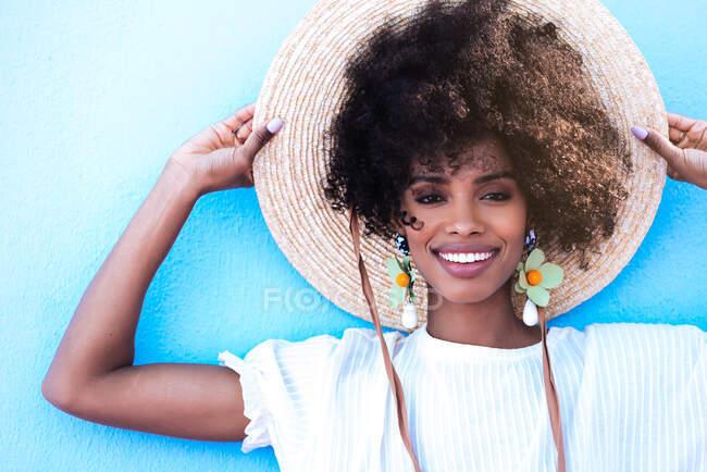 Красивая черная женщина, улыбающаяся в больших сережках и соломенной шляпе — стоковое фото