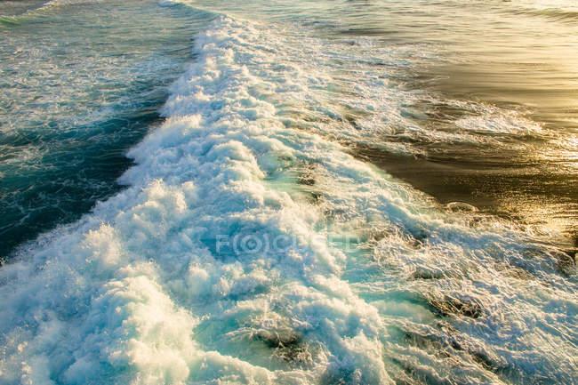 Onda oceanica con schiuma bianca pulita brillante rotolando sulla riva al tramonto — Foto stock