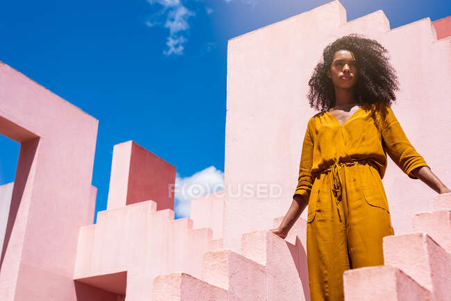 Black woman in a colorful geometric building stairs — Stock Photo