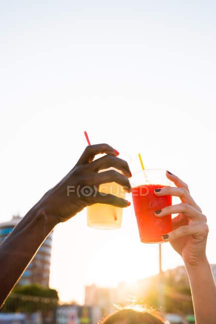 Mãos femininas clinking com copos de plástico de bebidas em luz solar brilhante na rua — Fotografia de Stock