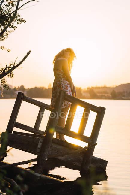 Женщина стоит на затонувшем пирсе в озере на закате — стоковое фото