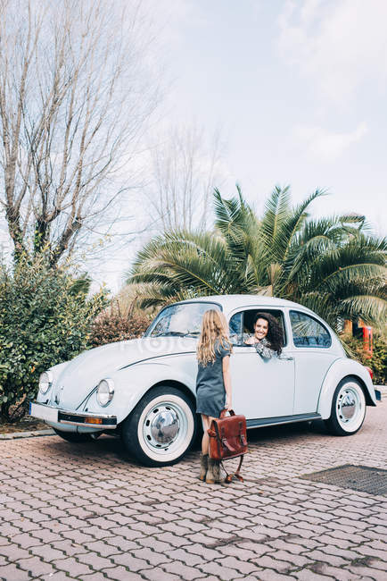 Blond girl walking in front of woman sitting in retro car in nature — Stock Photo
