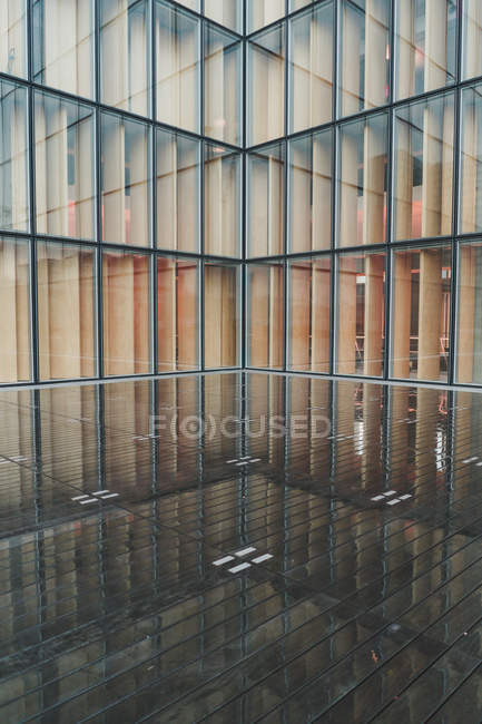 Glass walls of metropolis modern building and wet pavement — Stock Photo