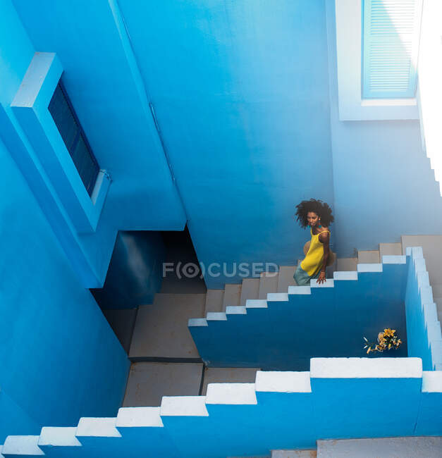 Black woman walking in a blue building stairs — Stock Photo