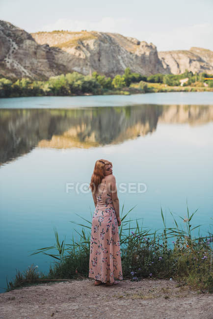 Woman in long summer dress standing on lake shore — Stock Photo