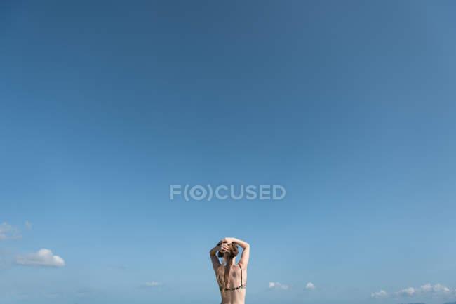 Вид сзади женщины, стоящей, регулируя волосы перед голубым небом — стоковое фото