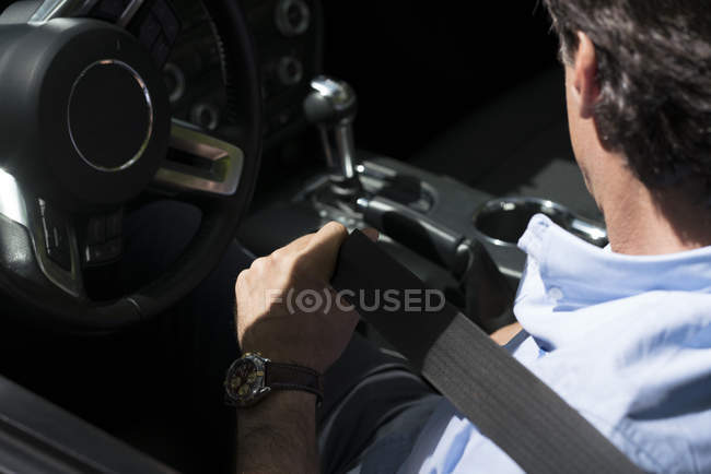 Close-up of man fastening belt in modern car — Stock Photo
