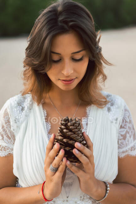 Charming elegant woman in white lace dress holding big pine cone and looking at it romantically — Stock Photo