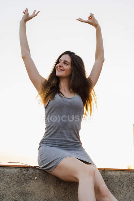 Happy woman sitting on wall outdoors and showing victory sign — Stock Photo