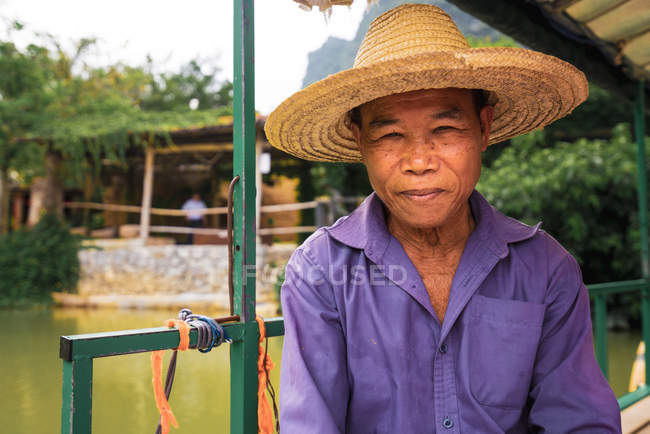 Smiling aged Asian fisherman in straw hat looking at camera outdoors — Stock Photo