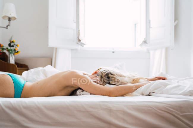 Mulher loira nua deitada em uma cama confortável no quarto aconchegante — Fotografia de Stock