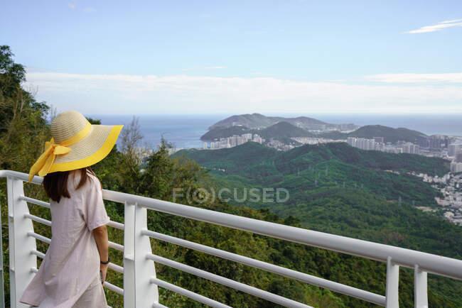Обратный вид женщины в шляпе, стоящей на террасе и наблюдающей живописный пейзаж с высоты зеленого парка Феникс и города, Китай — стоковое фото