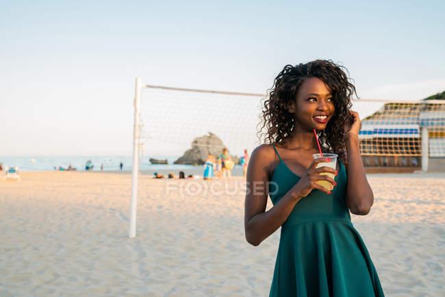 Элегантная черная женщина с напитком стоит на пляже и смотрит в сторону — стоковое фото
