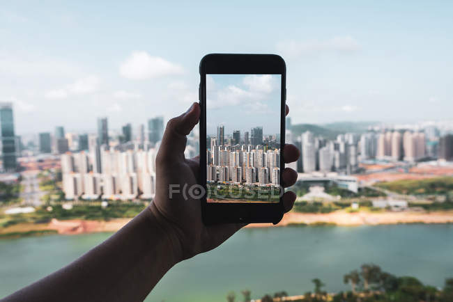 Human hand holding smartphone and taking picture of contemporary city of Nanning, China — Stock Photo