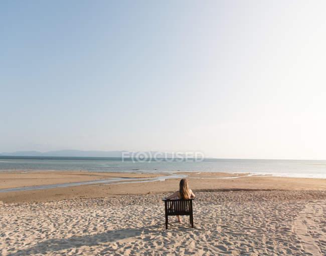 Задній вид жінка відпочиваючи на диван на піщаному пляжі і дивлячись на океан — стокове фото