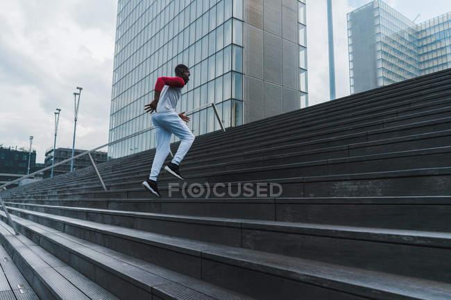 Молодий fit етнічних людина в спортивному одязі підбігаючи сходи зі скла сучасних будівель на тлі — стокове фото
