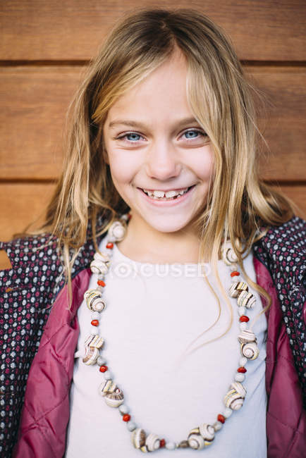 Portrait of smiling blond girl with blue eyes standing wooden background — Stock Photo