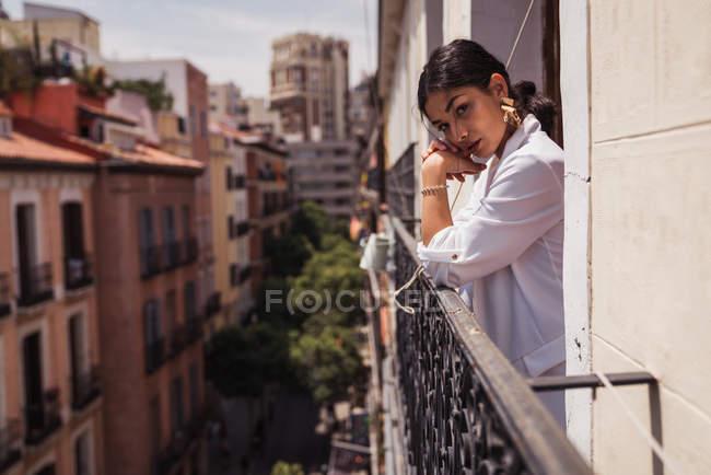 Alluring brunette woman in elegant white jacket and golden earrings standing on balcony — Stock Photo