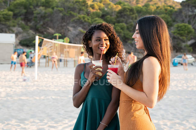 Young female friends chilling on beach with drinks in cups and laughing while chatting at sunset — Stock Photo