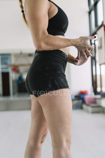 Female athlete with hands covered in chalk standing in gym during training — Stock Photo
