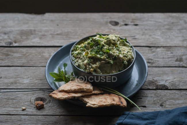 Tzatziki délicieux apéritif servi avec pain pita dans un bol sur la table en bois — Photo de stock