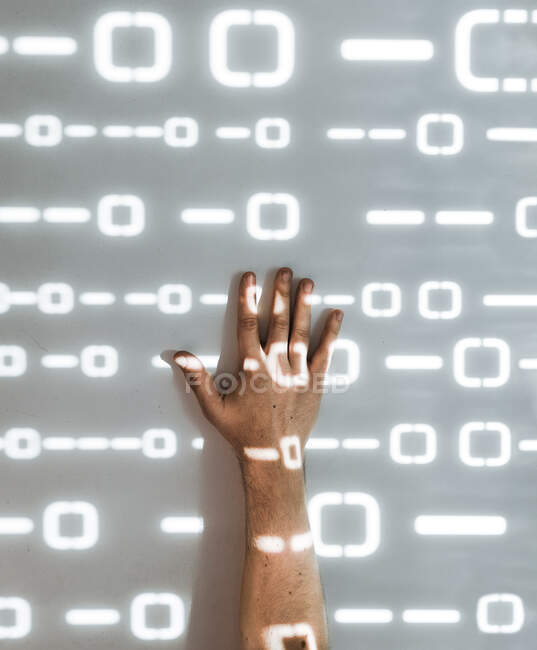 Crop hand and wall with futuristic geometric pattern made of light — Stock Photo