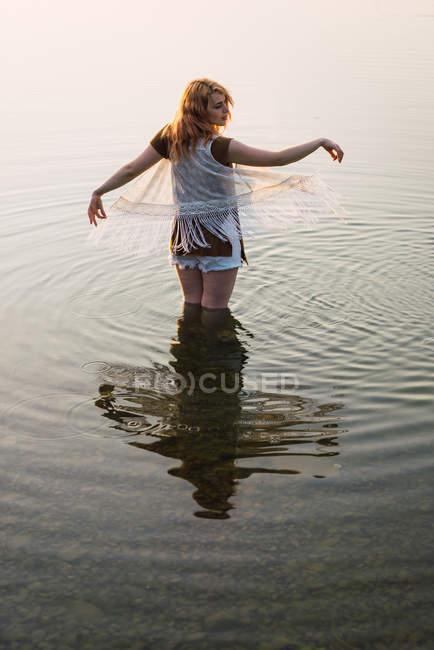 Жінка, стоячи в прозорій воді озера і жестикулюючи руками — стокове фото