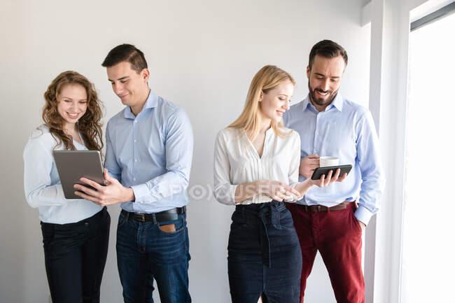 Мало хто з веселих елегантних чоловіків і жінок, стоячи разом у світлому кабінеті. — стокове фото