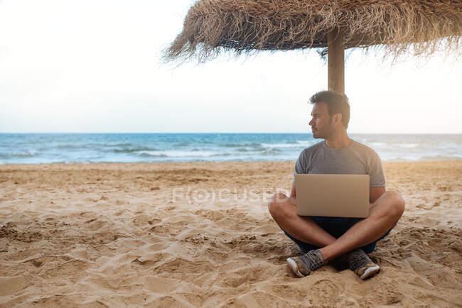 Мужчина, опирающийся на соломенный зонтик на пляже, работающий за компьютером — стоковое фото