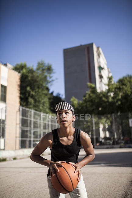 Young afro boy in cap playing basketball on court of neighborhood — Stock Photo