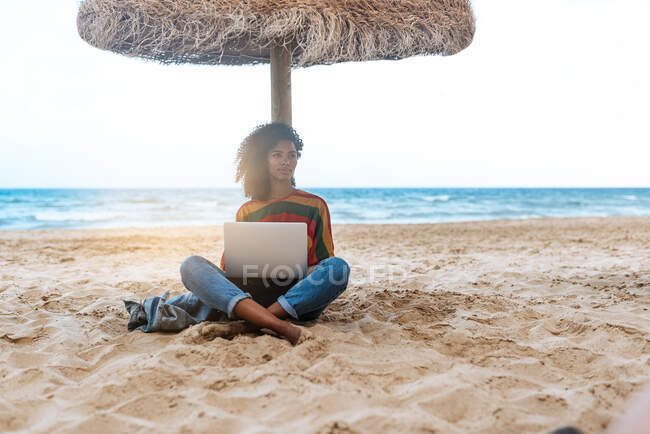 Woman leaning on a straw umbrella at the beach working on the computer — Stock Photo