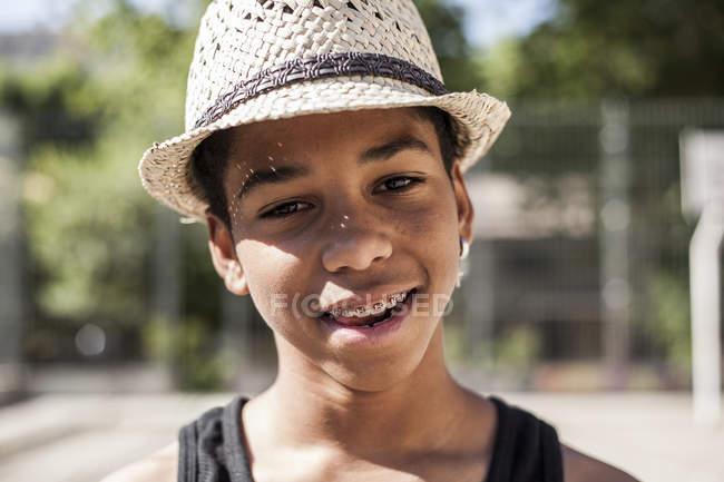 Усміхаючись молодий хлопчик у солом'яному капелюсі, стоячи на відкритому повітрі і, дивлячись на камеру — стокове фото