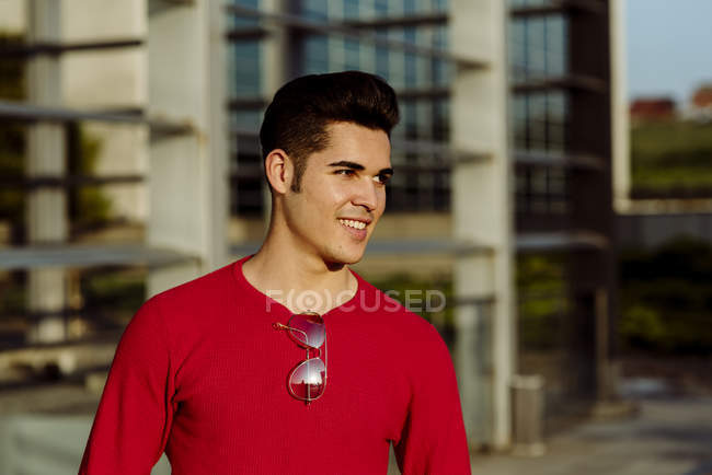 Portrait of young man standing in front of building and looking away — Stock Photo