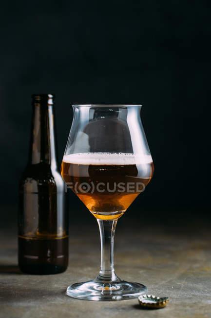 Бокал пива на темном фоне с бутылкой — стоковое фото