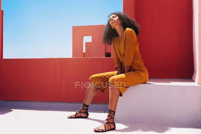 Чорна жінка сидить на барвистій терасі геометричного будинку. — стокове фото