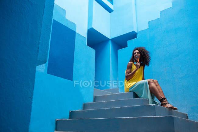Mujer negra sentada en un edificio azul escaleras con una paleta - foto de stock